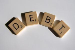 scrabble tiles spelling the word 'debt'